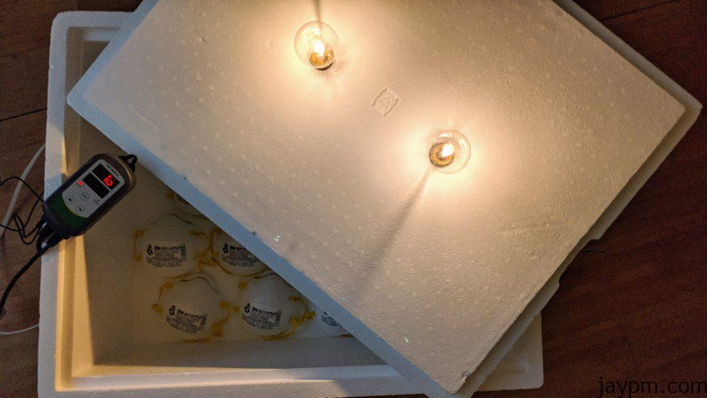 Two lightbulbs are mounted through the styrofoam cover